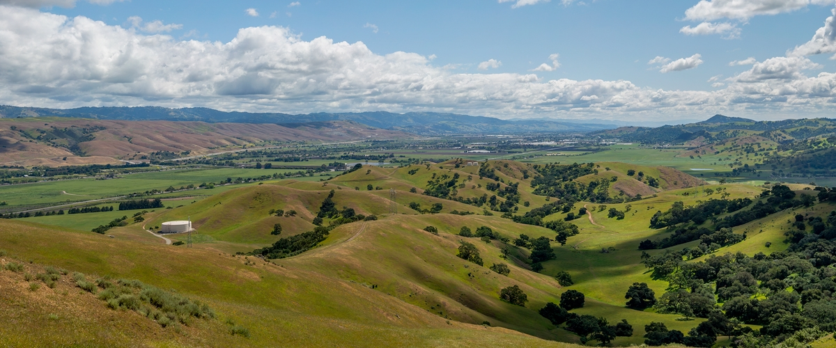 Expansive view looking south across Coyote Valley, with green fields, hillsides spotted with trees, mountains extending into the distance, and a sky filled with white fluffy clouds