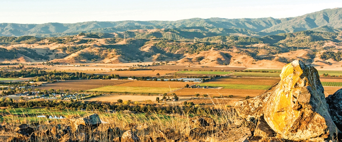 Looking down from a rock-covered hilltop at an expansive view of Coyote Valley's agricultural fields, the Santa Cruz foothills and mountains in the distance