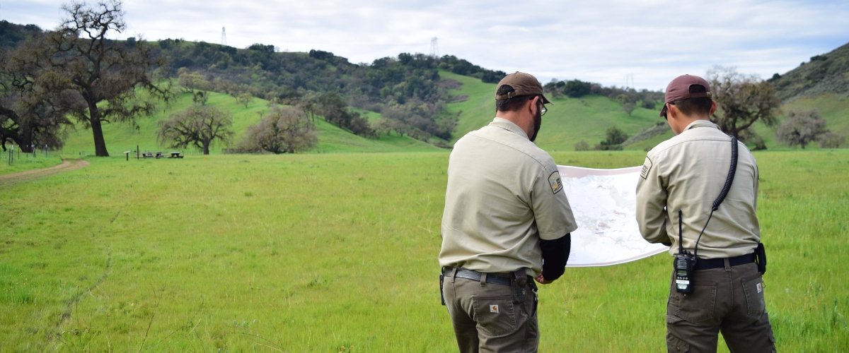 Two Open Space Technicians in tan and brown uniforms standing in green field and facing away from the camera, holding a large map in front of them