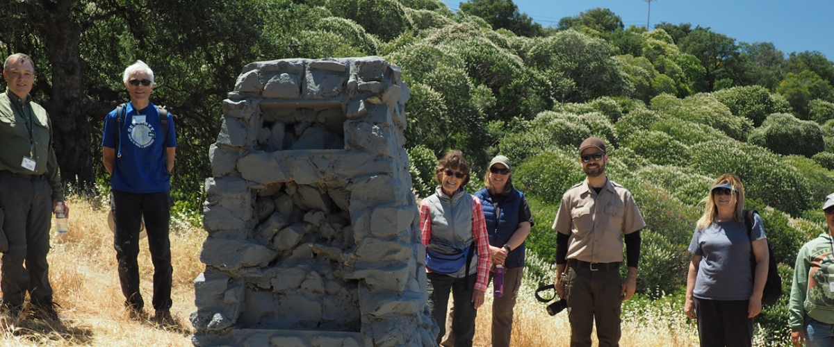Group of adult volunteers and one Open Space Technician smiling for picture on hillside next to stone structure