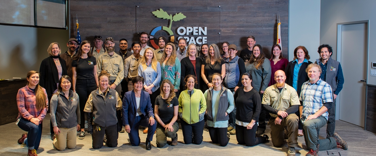 Group shot of Open Space Authority staff standing and smiling in front of agency sign