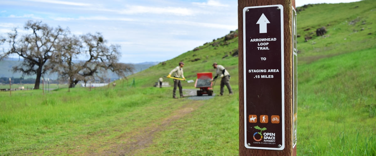 Arrowhead Loop trail marker in foreground, out of focus in the background are two Open Space Technicians in tan uniforms shoveling gravel onto the trail