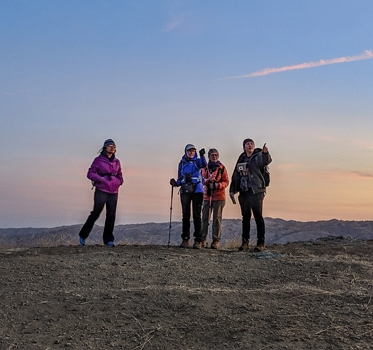Four hikers at top of hill pointing to the distance