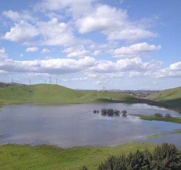 Laguna Seca wetland full of water surrounded by green hillsides under a blue sky