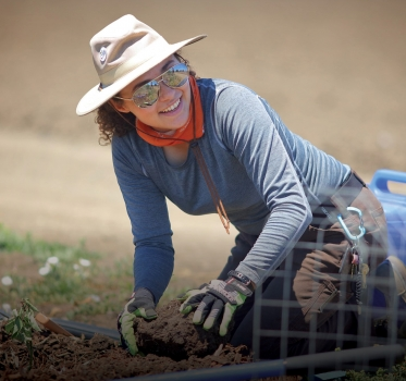 Smiling volunteer putting plant into ground