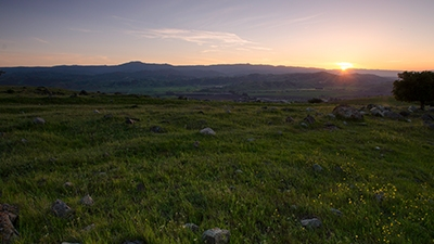 Grassy field with sun rising over distant mountains