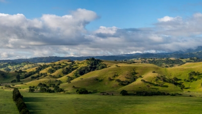 Green hills and field under blue sky with white clouds