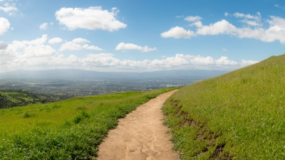 Dirt trail leading through green hills to view of San Jose in the distance below