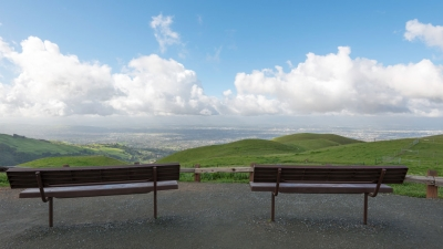 Two benches facing green hills and view of San Jose below in the distance