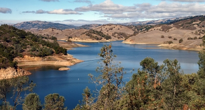 Blue Anderson Reservoir surrounded by brown hills and trees under a blue sky