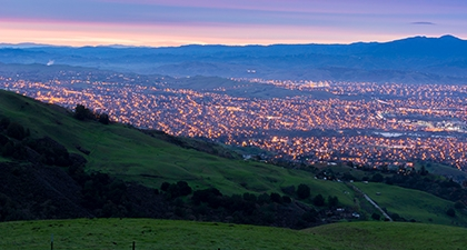 View from green hills of San Jose's city lights below, under a twilight sky