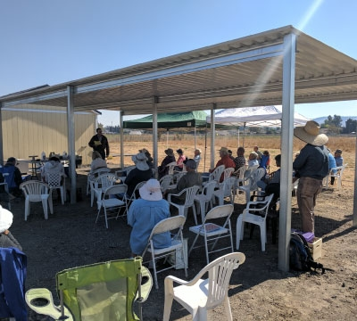 Group of people seated under outdoor shade structure
