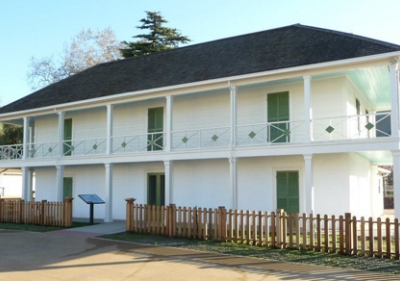 Alviso Adobe large, white two story house with wrap around porch and balcony