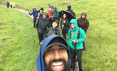 Young adult hikers in rain gear smiling on trail
