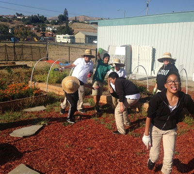 Students laughing and working in school garden