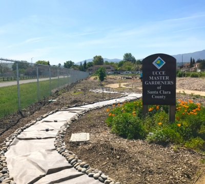 Path leading around garden and wooden sign with UC Master Gardeners of Santa Clara County name and logo