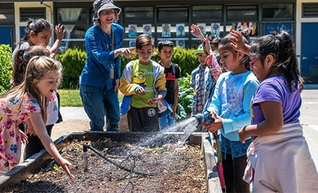 Smiling students and teacher around raised garden bed with sprinkler hose
