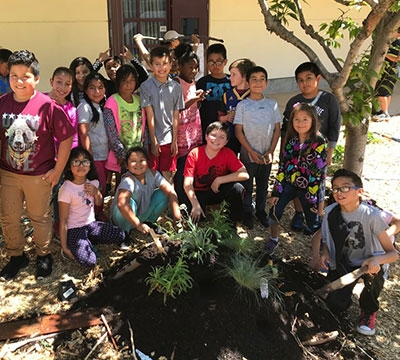 Group of students smiling around garden bed