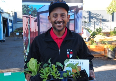 Valley Verde representative holding tray of plants in containers with garden in background