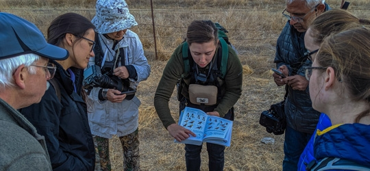 Woman holding bird identification book open to group of hikers around her