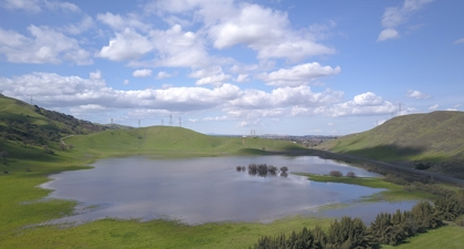 Laguna Seca wetland full of blue water surrounding by green hillsides