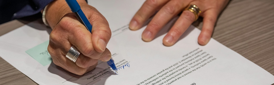 Close up of hands signing document