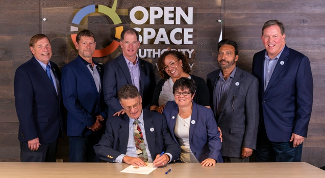 Open Space Authority Board Members and General Manager Andrea Mackenzie signing document in front of agency logo sign