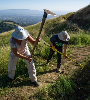 Two volunteers working with tools on a Sierra Vista trail