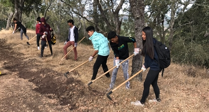 Group of middle school students working with tools on a hiking trail surrounded by trees