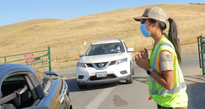 Open Space Technician in face mask and neon vest greeting preserve visitors in car