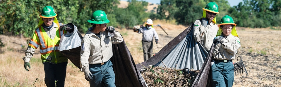 Workers in green hard hats clearing trash and debris at Fisher's Bend property