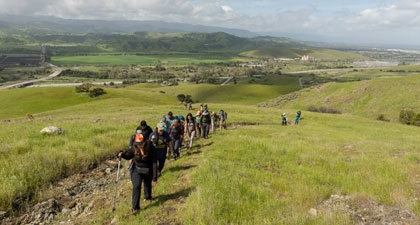 Line of hikers walking up trail at Coyote Ridge, sweeping view of Coyote Valley below