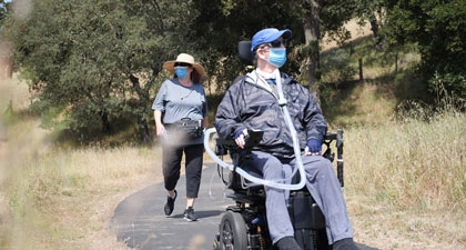 Man in wheelchair and woman walking behind on nature trail, both wearing face masks