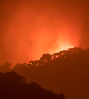 Silhouettes of hillsides with red sky and burning fire behind them