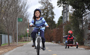 Smiling girl in striped sweater riding a bicycle on paved trail, young boy on tricycle in background