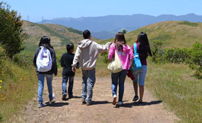 Group of five young adolescents walking away from camera on trail with green hills in distance