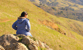 Young woman in blue jacket sitting on rocks taking in view of green hills