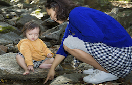 Mother in blue shirt and checkered skirt pointing something out to toddler in orange shirt sitting on rocks