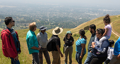 Group of family hikers at Sierra Vista overlooking cityscape below