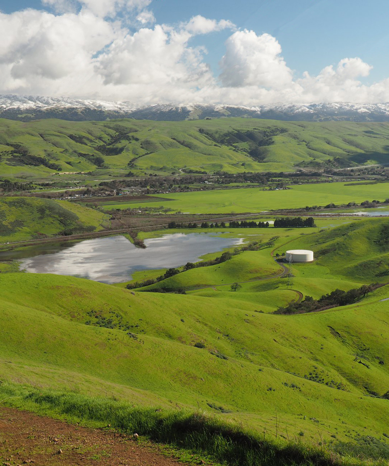 Image of green hillsides surrounding Laguna Seca wetland full of water