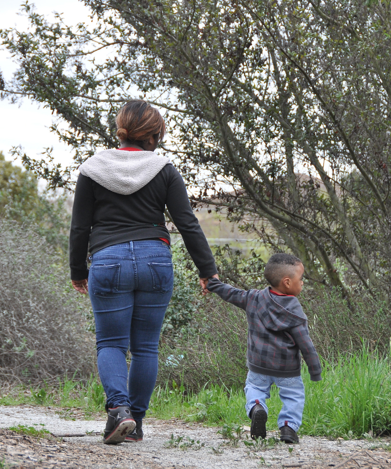 Mother holding hands with small child walking away on a nature trail