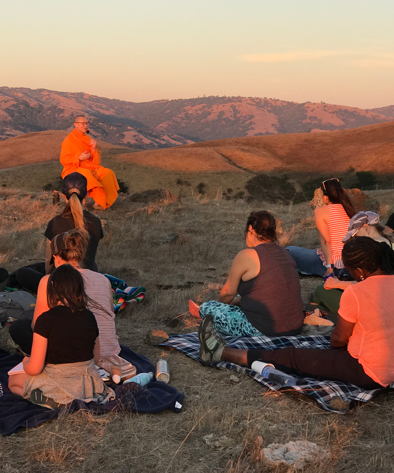 monk in orange robes leading meditation session on top of Coyote Ridge at sunset