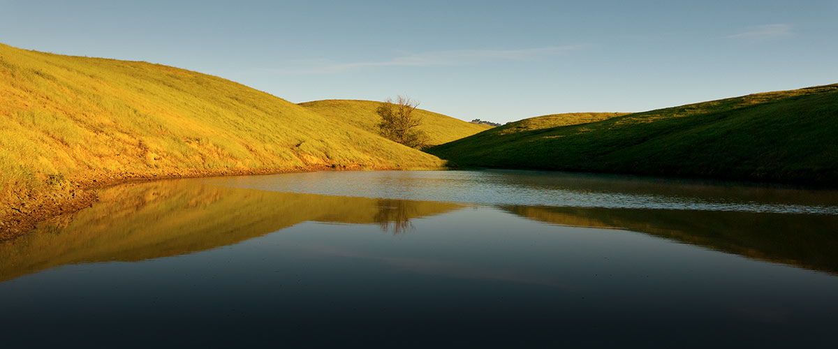 Full pond surrounded by bright green hills under a clear blue sky, the water reflecting the hillsides and sky