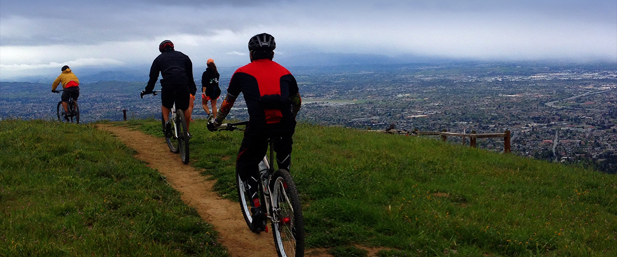 Three mountain bikers and two hikers traveling along dirt trail at top of grassy hill overlooking urban San Jose below