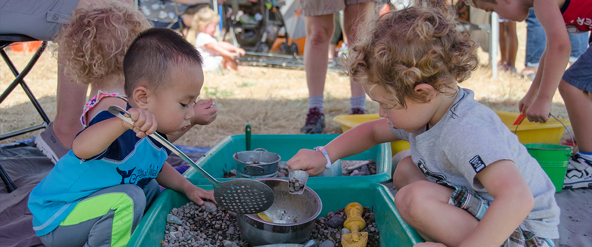 Two toddlers playing with a nature activity at an outdoor community event