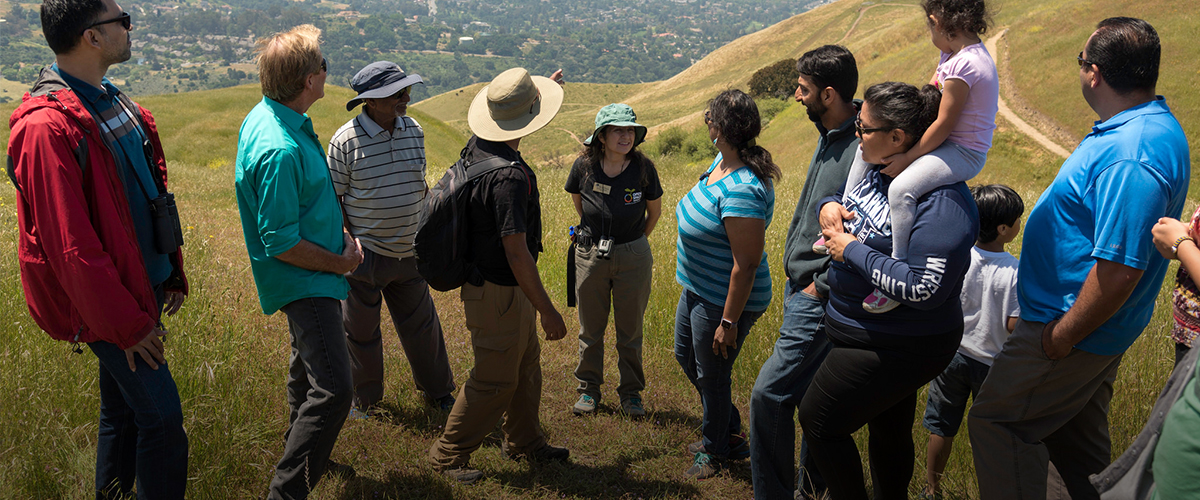 Group of 12 adults and children taking in the view at the top of Sierra Vista, surrounding a female volunteer in an Open Space Authority t-shirt
